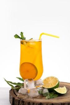 Лимонный коктейль, вид спереди с кубиками льда и соломкой на белом, цвет напитка сока