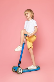 正面ピンクの床に白いtシャツ乗馬スクーターでかわいい男の子金髪髪かわいい