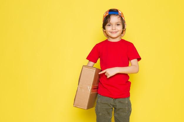 Вид спереди маленький мальчик в красной футболке красочной кепке и брюки цвета хаки, держа коробку на желтом фоне