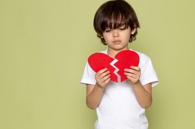 Вид спереди маленького мальчика в белой футболке, держащего разворачивающуюся сердечко на каменном цветном пространстве