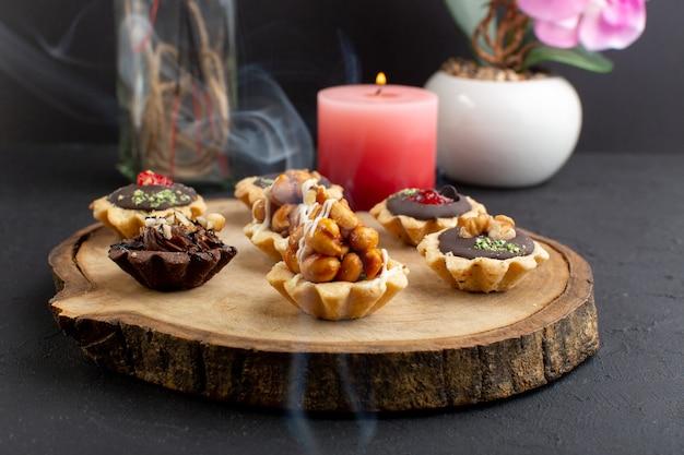 Вид спереди маленькие пирожные с ореховым песком и шоколадом на деревянном столе и темном фоне цвета сладкого сахарного торта