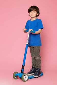 Вид спереди маленького ребенка в синей футболке верхом на самокате на розовом полу