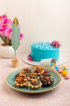 Вид спереди вкусные шоколадные пирожные вместе с голубым праздничным тортом на розовом столе