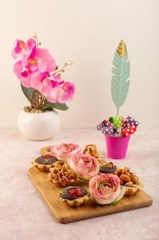 ピンクの机の上の花と正面の小さなチョコレートケーキ
