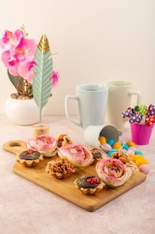 正面にピンクの机の上の花と植物の小さなチョコレートケーキ