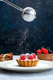 正面図の白いプレート内にクリームとフルーツが入った小さなおいしいケーキ、グレーブルーのデスクフルーツケーキに砂糖の粉が入った新鮮なフルーツ