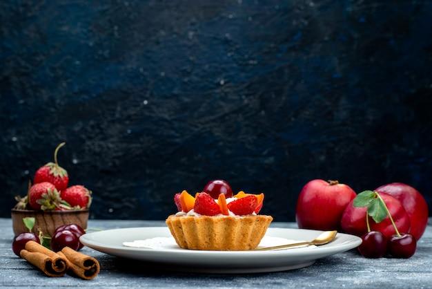 正面図クリームとフルーツの入った小さなおいしいケーキとグレーのブルーのデスクのフルーツケーキビスケットのフレッシュフルーツ