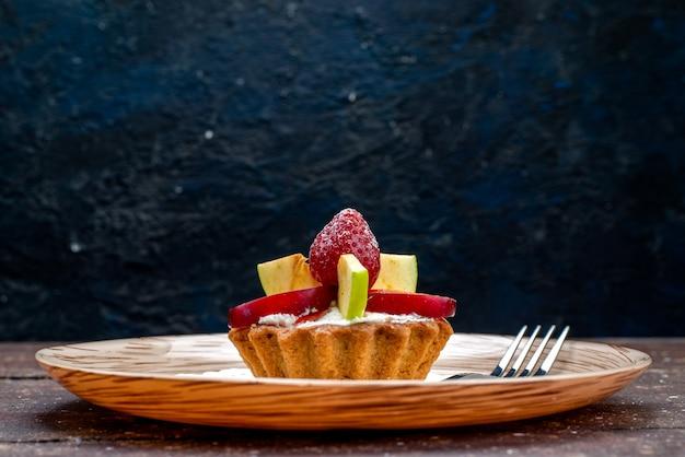 Вид спереди маленький вкусный торт со сливками внутри тарелки со свежей нарезанной клубникой и яблоками на темном фоне, печенье, бисквитный торт, фрукты