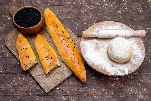 Вид спереди длинный испеченный хлеб с мукой и тестом на темном тесте для выпечки хлеба на столе