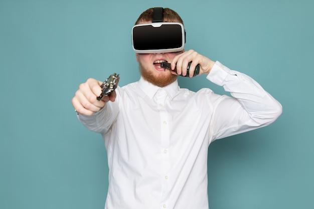 Вид спереди человек с пистолетом и гранатой играет vr в белой футболке на синем полу