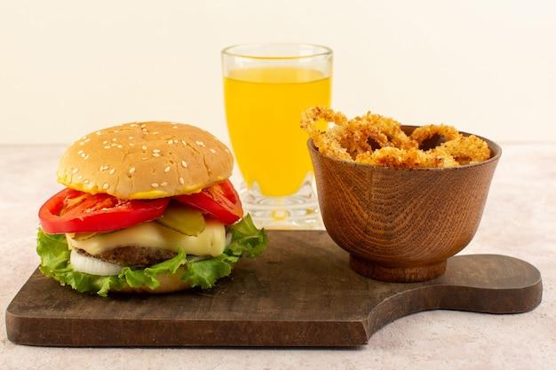 木製のテーブルの正面図肉チーズバーガーとチーズジュースとグリーンサラダと手羽先