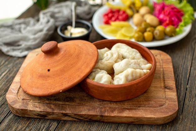 Вид спереди мясной муки с мясом и свежими овощами на коричневом деревянном деревенском столе
