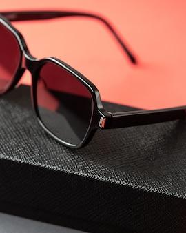 Вид спереди современные черные очки на розово-темных