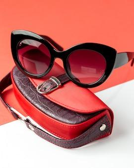 Вид спереди современные темные очки вместе с красной кожаной сумкой на бело-красном