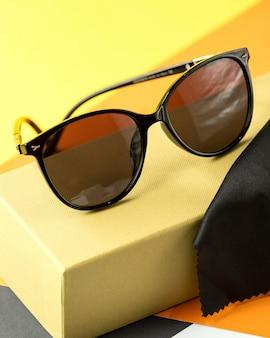 Вид спереди современные темные очки на оранжево-черном
