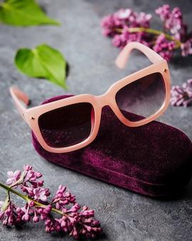 Вид спереди современные розовые очки на сером