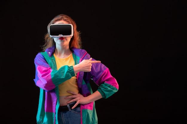 カラフルなコートオレンジのtシャツで正面のモダンな若い女性が黒の背景のゲームのインタラクティブなプレイで仮想現実を再生