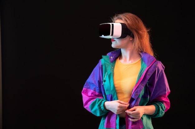 Вид спереди современной юной леди в красочном пальто оранжевой футболке, играющей виртуальную реальность на черном фоне игровой интерактивной игры
