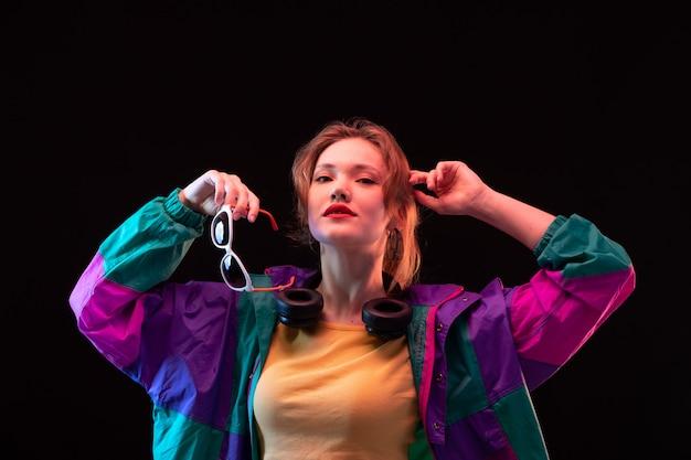 검은 이어폰과 선글라스 검은 배경에 포즈 현대 패션에 화려한 코트 오렌지 티셔츠에 전면보기 현대 젊은 아가씨