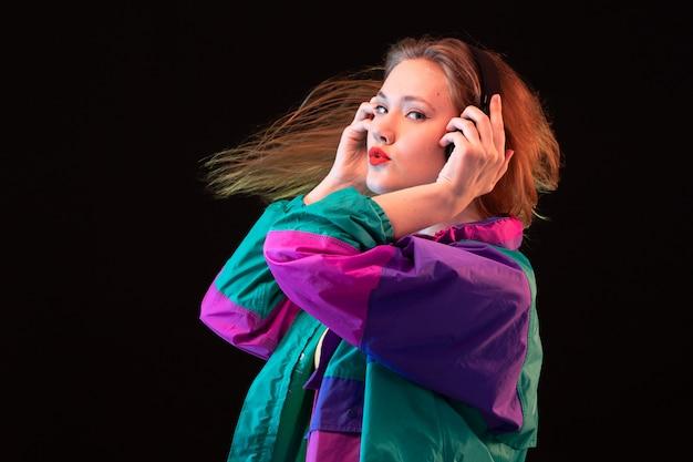 カラフルなコートオレンジ色のtシャツで正面のモダンな若い女性黒い背景の音楽を聴いてポーズをとって黒いイヤホンダンスモダンなファッション
