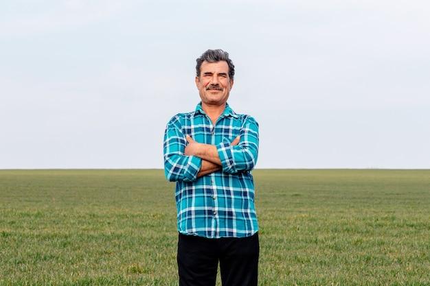 Вид спереди портрет счастливого владельца-фермера со скрещенными руками в поле