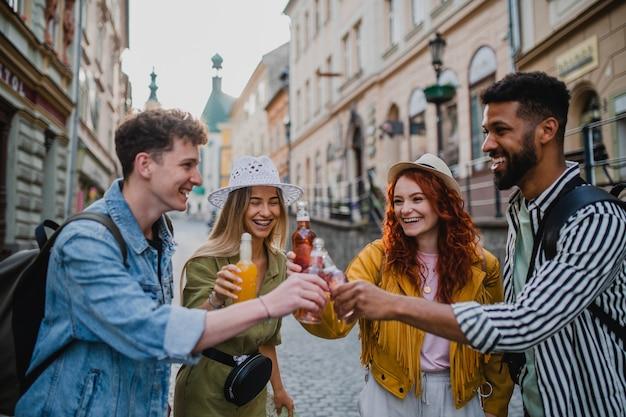마을 여행에서 야외에서 술을 마시며 웃고 있는 행복한 젊은이들의 앞모습.