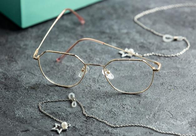 청록색 선글라스 상자와 실버 팔찌 고립 된 시력 눈을 가진 회색 책상 근처 전면 광학 선글라스
