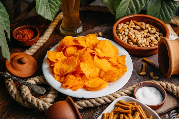 Вид спереди апельсиновые чипсы с арахисом и солью на деревянном столе чипсы для закусок соленые специи