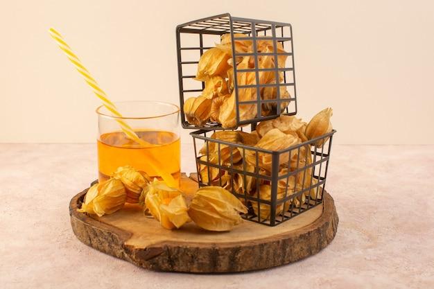 Очищенный апельсиновый физалис, вид спереди, в черной корзине с напитком на розовом столе