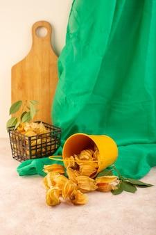 ピンクの机の上の緑色のティッシュでバケツの中にオレンジ色の皮をむいたサイサリスの正面図
