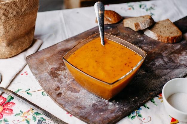 正面にあるオレンジ色のペッパースーププレートの内側のプレートは、茶色の机の上のパンのローフミール液と一緒にスプーンでおいしい塩味