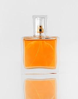 Вид спереди оранжевые духи внутри стекла, изолированные на белом полу