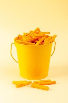 Макаронные изделия спереди в корзине сформировали оранжевое сырье внутри желтой корзины на кремовой пасте