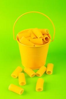 バスケットの中の正面パスタは、緑の背景の食事食品イタリアンスパゲッティに黄色のバスケットの中に生を形成