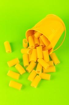 Макаронные изделия спереди внутри корзины сформировали сырцовые внутри желтой корзины на зеленой предпосылке еду еды итальянские спагетти