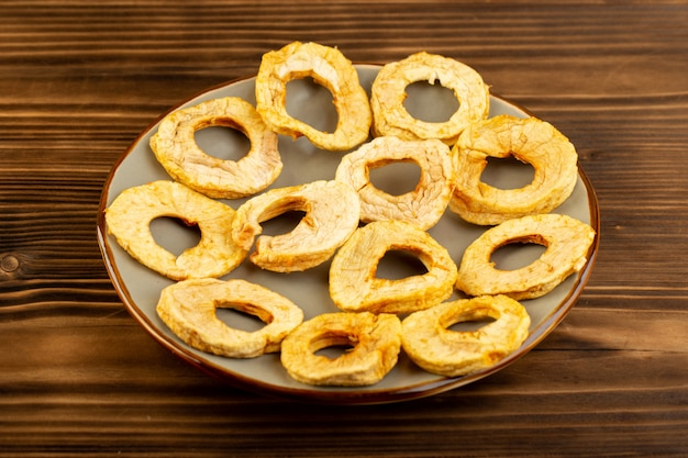Вид спереди ананас сушеные кольца внутри тарелки сухофрукты кислый вкусный уникальный вкус на коричневом деревянном столе фрукты экзотические сухие