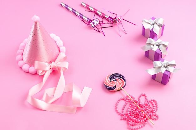 Вид спереди розовые декорации дня рождения маленькие фиолетовые подарочные коробки, смычки, сладкий леденец, изолированный на розовом