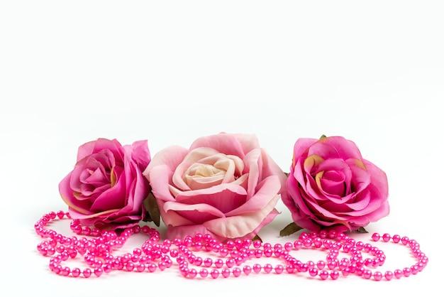 正面のピンクのバラと白い机の上のピンクのネックレス