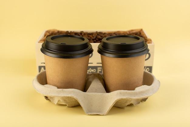Вид спереди пластиковые кофейные чашки с доставкой кофейной пары на желтой стене