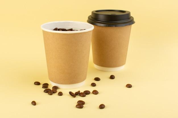 黄色の表面に茶色のコーヒーの種を正面から見たプラスチック製のコーヒーカップ