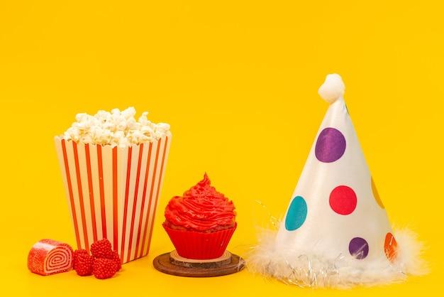 正面のポップコーンと黄色の机の上のマーマレードと誕生日キャップ付きケーキ