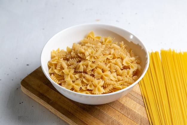木製のテーブルパスタイタリア料理の食事に形成された少し長く形成された生のイタリアンパスタの正面図
