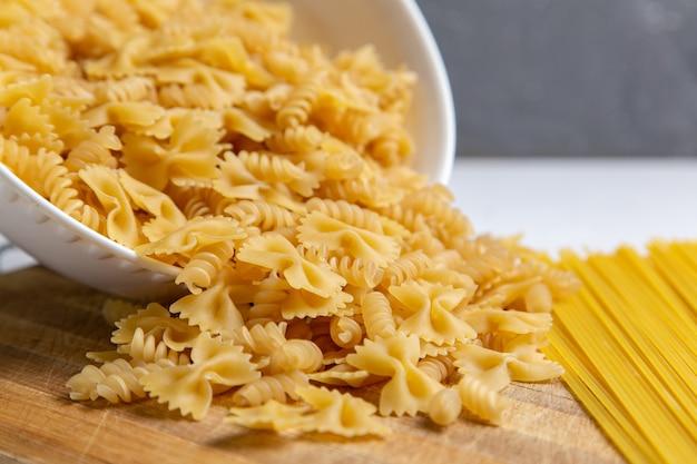 Вид спереди сырой итальянской пасты, немного сформированной на деревянном столе, паста итальянская еда
