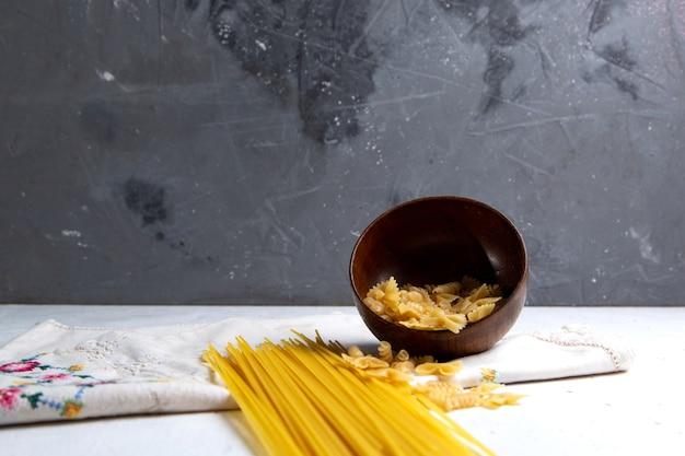 Вид спереди сырые итальянские макароны, длинная и маленькая миска для макарон