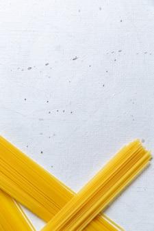 白いテーブルパスタイタリア料理の食事で長く形成された正面生パスタ