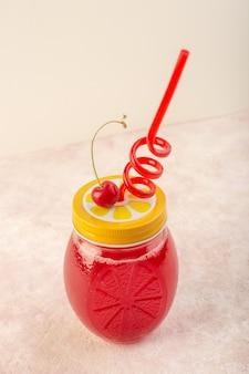 正面の赤いチェリーカクテルフレッシュでピンクの机の上にストローでアイシングジュースジュース色のフルーツ