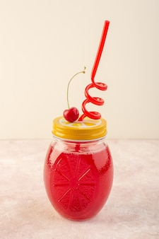 Красный вишневый коктейль с соломкой на розовом столе, вид спереди, свежий фруктовый напиток