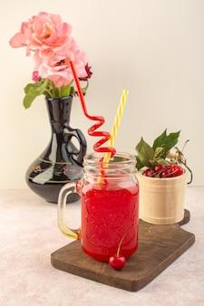 Коктейль с красной вишней, вид спереди, соломкой и вишней на розовом столе.