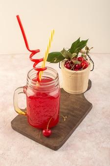 ピンクのデスクフルーツ色のドリンクジュースにストローとチェリーの正面図レッドチェリーカクテル