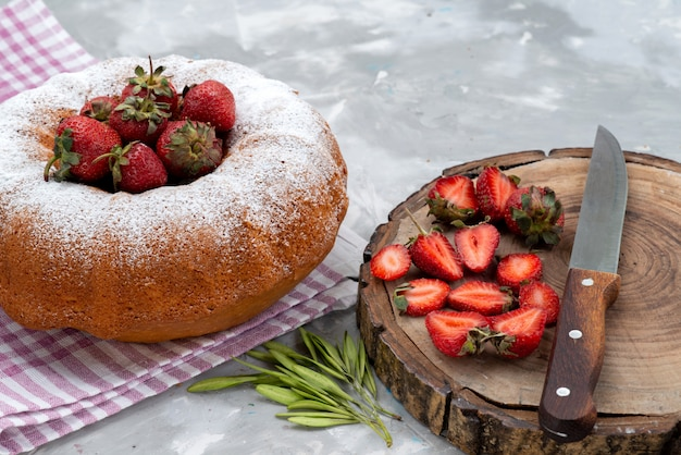 Круглый торт с сахарной пудрой и красной клубникой на белом столе, ягодный фруктовый торт, вид спереди